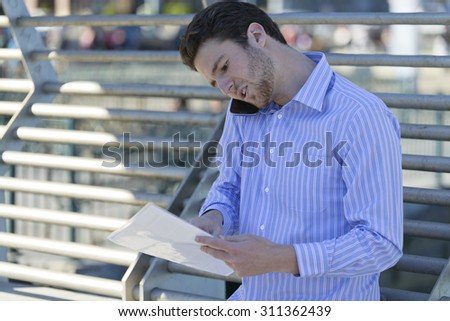Young man takes a business call outdoors - stock photo