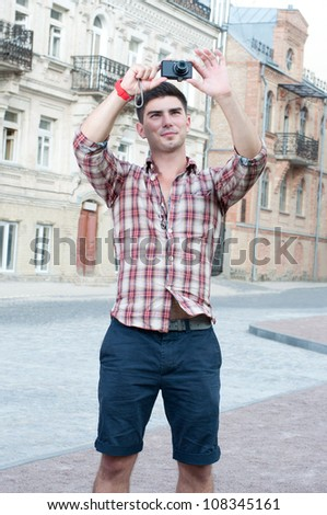 Young man takes to the camera city attractions. - stock photo