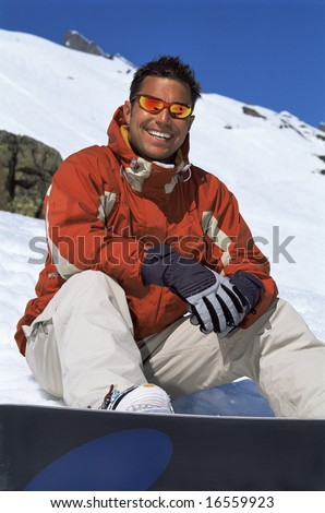 Young man taking a break from snowboarding - stock photo