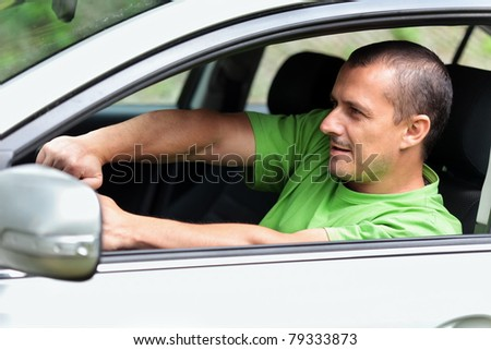 Young man taking a fast turn in his sports car - stock photo