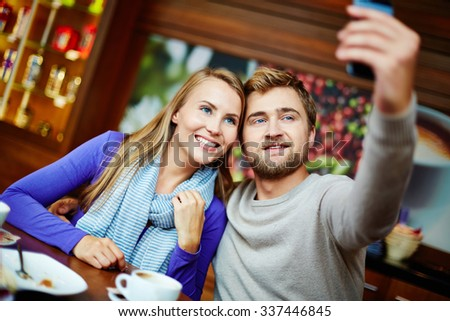 Young man taking a photo with his mobile phone in a cafe