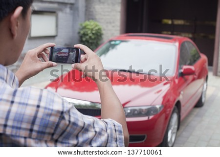 Young Man Taking a Picture of His Car - stock photo