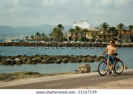 Young man taking a ride on a bicycle along the seashore - stock photo