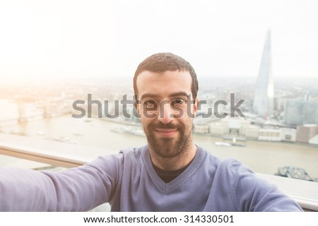 Young man taking a selfie with London cityscape on background. He is holding a smart phone and looking at it smiling.