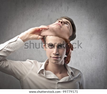 Young man taking off a mask - stock photo
