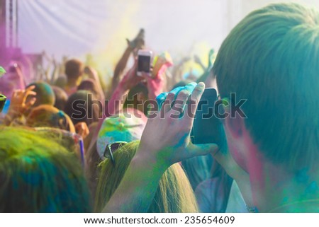 Young man taking photo on mobile phone on holi color festival - stock photo