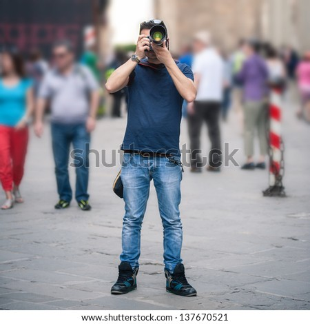 Young man taking photo with professional camera in a city with crowd. - stock photo