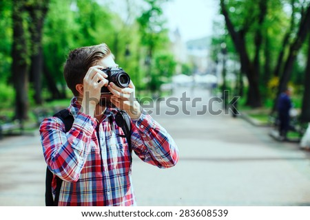 Young man taking photos on old film camera outdoors in the alley, in the park, profile - stock photo