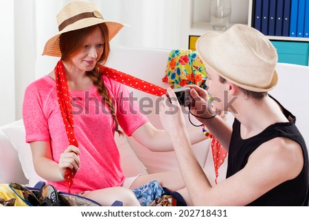 Young man taking picture of woman trying clothes