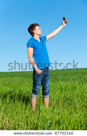 young man taking picture on phone against green grass and blue sky - stock photo
