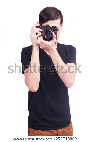 Young man taking picture with film camera isolated - stock photo