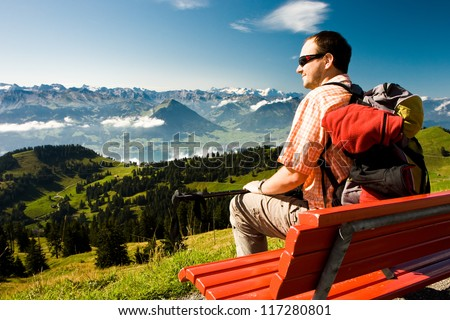 Young man taking rest on the top of the Rigi mountain in Swiss Alps, Central Switzerland - stock photo