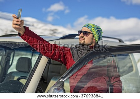 Young man taking selfie picture with smart phone camera after driving in new white car outdoors. Selfie on snowy slope with the beautiful snow capped Alps in the background. Winter time natural colors - stock photo