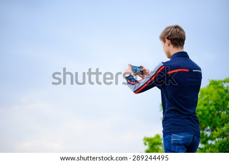 Young Man Taking the Landscape Photograph Using Mobile Smart Phone - stock photo