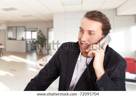 Young man talking at phone in an office environment