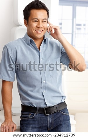 Young man talking on mobilephone, smiling happy, looking away. - stock photo