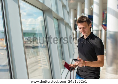Young man talking on phone inside the airport - stock photo