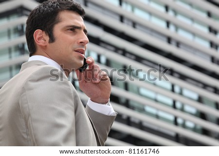 Young man talking on phone outdoors - stock photo