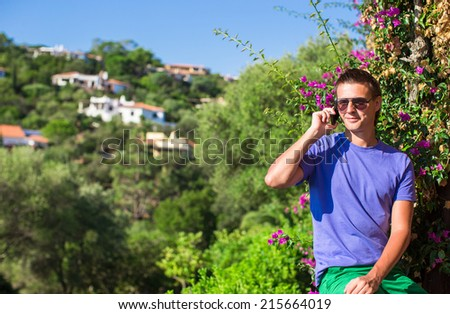 Young man talking on the phone at the balcony - stock photo