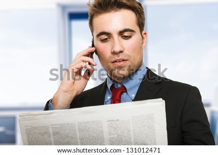 Young man talking on the phone while reading the newspaper - stock photo