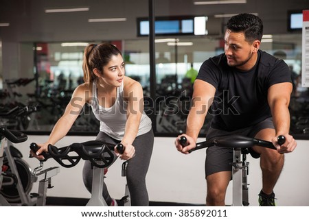 Young man talking to a cute brunette while they both do some cardio on a bicycle at the gym. Focus on woman - stock photo