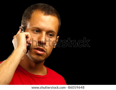 young man talking with the mobile phone on black background - stock photo