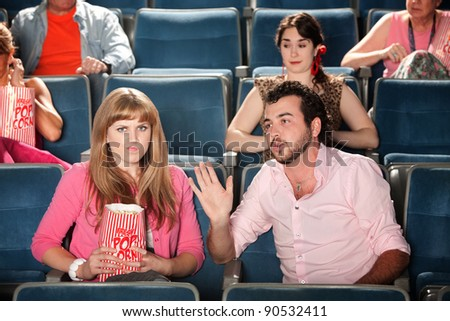 Young man talks out loud with annoyed woman in theater - stock photo