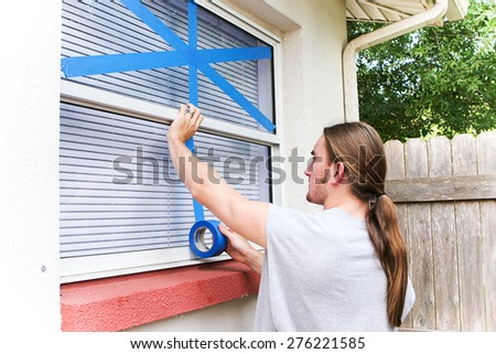 Young man taping up windows in preparation for a hurricane.   - stock photo