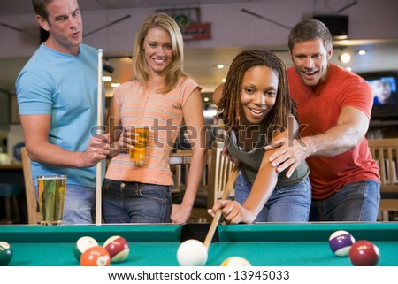 Young man teaching a young woman to play pool - stock photo