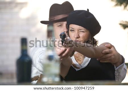 Young man teaching his girlfriend to shoot - stock photo