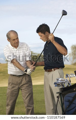 Young man teaching senior man to play golf - stock photo