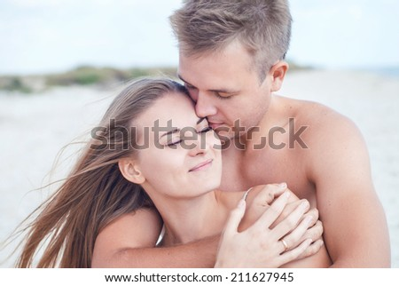 young man tenderly embracing and kissing young woman on a beach