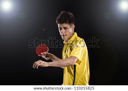 young man tennis-player in play on black background with lights - stock photo