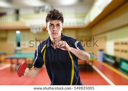 young man tennis-player in play on sport club background - stock photo