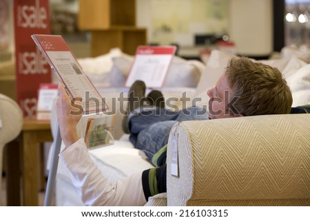 Young man testing sofa in shop, rear view - stock photo