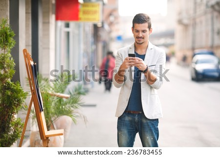 Young man text messaging on the street - stock photo