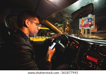 Young man texting and driving. Teenage driver on his cellphone while driving his car at night. Typing on the smartphone at the traffic lights. Dangerous driving concept. - stock photo