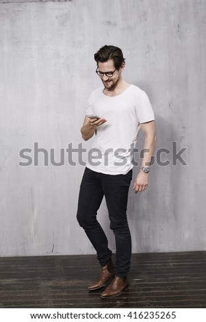 Young man texting on cell phone in studio