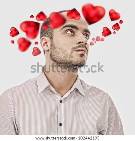 Young man thinking about love. Red hearts are flying around his head - stock photo
