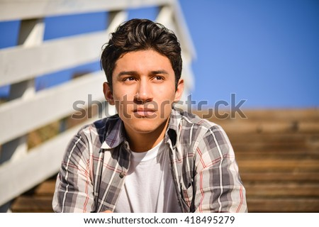 Young man thinking outside. Sitting on steps, looking into the distance - stock photo