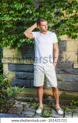 Young man thinking. Wearing a white V neck T shirt, light yellow shorts,  leather shoes, a hand scratching the back of head, a young guy is standing by a wall with green ivy leaves, waiting, thinking. - stock photo