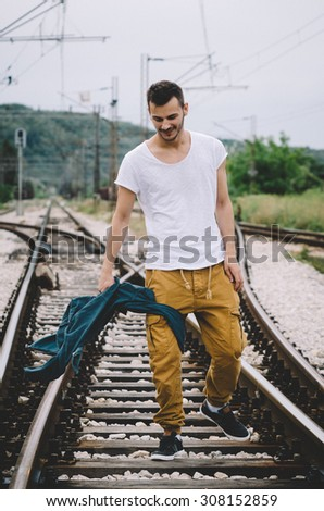 Young man throwing a jacket on the railroad. Vintage Instagram style effect, soft and selective focus, grain texture visible on maximum size - stock photo