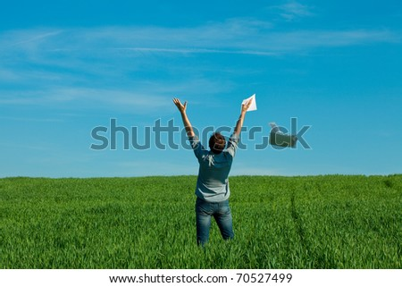 young man throwing a paper in the green field - stock photo