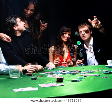 Young man throwing chips on the table while playing cards - stock photo
