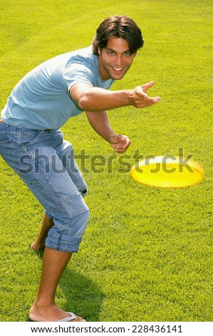 Young man throwing frisbee - stock photo