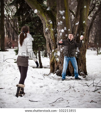 Young man throwing snowball in his girlfriend - stock photo