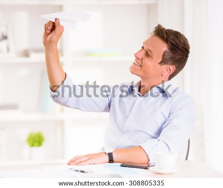 Young man throws paper plane and smiling. - stock photo