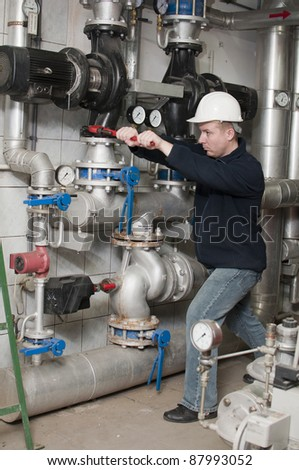 young man tightened the screw a big pipewrench - stock photo