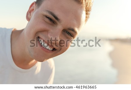Young man to peep at lens on the beach