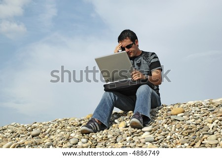 young man to the computer in top of the legs, to the outdoors... - stock photo